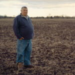 最近収穫が終わり、次の植え付けを待つ畑に立つジョージ。